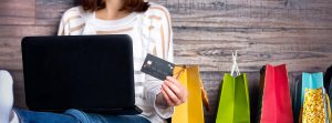 Woman sat at laptop with credit card and shopping bags highlighting the problem with customer returns